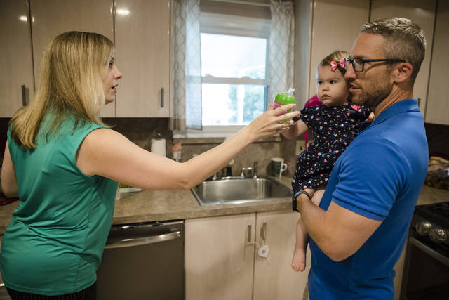 In this Aug. 1, 2018 photo, Lauren Woehr hands her 16-month-old daughter Caroline, held by her husband Dan McDowell, a cup filled with bottled water at their home in Horsham, Pa. In Horsham and surrounding towns in eastern Pennsylvania, and at other sites around the United States, the foams once used routinely in firefighting training at military bases contained per-and polyfluoroalkyl substances, or PFAS. EPA testing between 2013 and 2015 found significant amounts of PFAS in public water supplies in 33 U.S. states. (AP Photo/Matt Rourke)