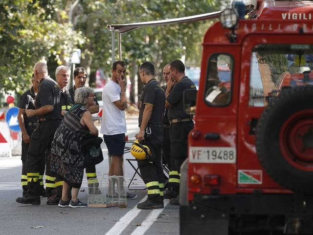A woman talks to firefighters as they accompany residents to get their belongings from their homes, in Genoa, Italy, Thursday Aug. 16, 2018. Authorities worried about the stability of remaining large sections of a partially collapsed bridge evacuated about 630 people from nearby apartments, some practically in the shadow of the elevated highway. (AP Photo/Antonio Calanni)