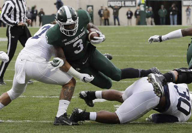 File- This Nov. 4, 2017, file photo shows Michigan State running back LJ Scott (3) being  tackled by Penn State linebacker Koa Farmer, left, during the first half of an NCAA college football game in East Lansing, Mich. Scott enters his senior season with some impressive career rushing stats: 2,591 yards and 25 touchdowns. A good final season could put him in the top four on the school's career list in both categories but he also has room for improvement. He was part of a team-wide fumbling problem that plagued the Spartans last year. (AP Photo/Carlos Osorio, File)