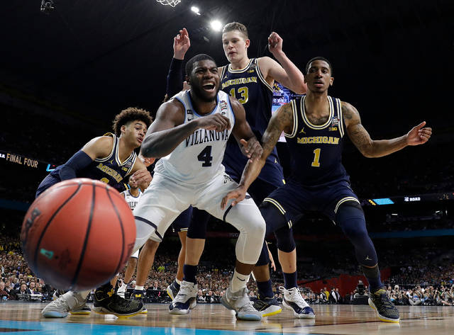 FILE - In this Monday, April 2, 2018 file photo, Villanova's Eric Paschall (4) reacts as he loses the control of the ball against Michigan's Moritz Wagner (13) and Charles Matthews (1) during the first half in the championship game of the Final Four NCAA college basketball tournament in San Antonio. The NCAA has a new ranking system to replace RPI when evaluating college basketball teams for the NCAA Tournament. The NCAA Evaluation Tool announced on Wednesday, Aug. 22, 2018 will rely on game results, strength of schedule, game location, scoring margin, net offensive and defensive efficiency and quality of wins and losses. NET will be used for the 2018-19 season by the committee that selects schools and seeds the tournament.(AP Photo/Eric Gay, File)
