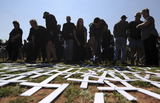 "In this photo taken Oct. 30, 2017 people place white crosses, symbolically representing farmers killed in the country, at a ceremony at the Vorrtrekker Monument in Pretoria, South Africa. U.S. President Donald Trump has tweeted that he has asked the Secretary of State Mike Pompeo to ""closely study the South African land and farm seizures and expropriations and the large scale killing of farmers."" Trump added, ""South African Government is now seizing land from white farmers."" (AP Photo)"