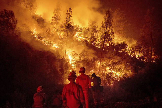 FILE - In this Aug. 7, 2018 file photo, firefighters monitor a backfire while battling the Ranch Fire, part of the Mendocino Complex Fire near Ladoga, Calif. A nationwide telecommunications company that slowed internet service to firefighters as they battled the largest wildfire in California history says it has removed all speed cap restrictions for first responders on the West Coast. Verizon Senior Vice President Mike Maiorana says the service restrictions were removed as of Thursday, Aug. 23, 2018, and include Hawaii, where emergency crews have rescued people from areas flooded by Hurricane Lane. (AP Photo/Noah Berger, File)