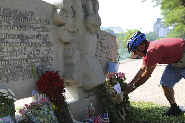 Pham Van Khanh, a 62-year-old retiree, lays flowers at the monument of Senator John McCain in Hanoi, Vietnam, Monday, Aug. 27, 2018. The monument was erected by Vietnamese authority to mark the day when McCain's plane, a Major in the U.S. Navy was shot down in 1967. Vietnam has been paying respect to McCain who died on Saturday. (AP Photo/Tran Van Minh)