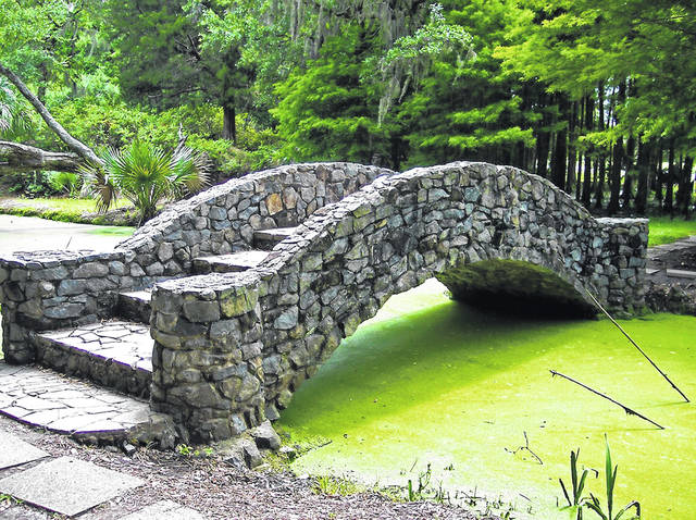 The stream this bridge crosses is filled with green algae.