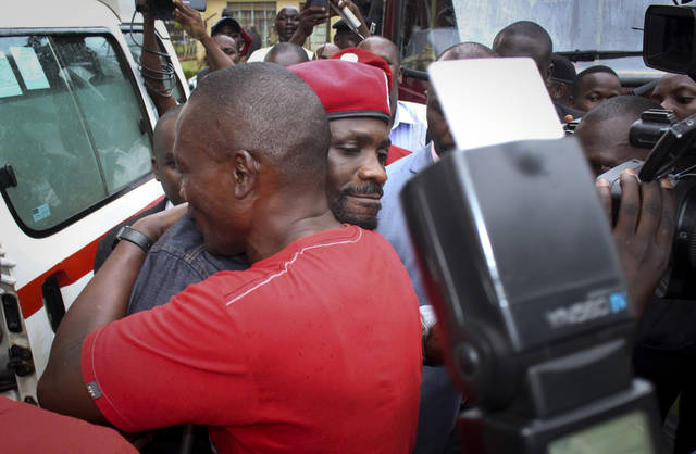Ugandan pop star Kyagulanyi Ssentamu, better known as Bobi Wine, center, wears a beret and is hugged by a supporter as he gets into an ambulance after leaving the courthouse in Gulu, Uganda Monday, Aug. 27, 2018. The 36-year-old lawmaker, who has been in detention since Aug. 14 and faces charges of treason, was freed on bail Monday by a judge in the northern Ugandan town of Gulu. (AP Photo)