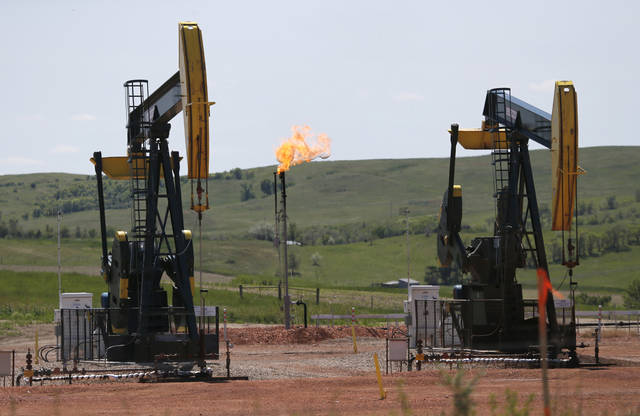 FILE -In this June 12, 2014 file photo, natural gas is burned off near pumps in Watford City, N.D. As Trump rolls back some Obama-era rules on climate-changing methane pollution, Colorado officials say their regulations have reduced oil field leaks. A report released Thursday, Aug. 23, 2018, shows required state inspections helped find and repair 73,000 methane leaks over three years. (AP Photo/Charles Rex Arbogast, File)
