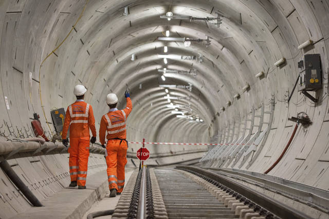 FILE - In this Sept. 14, 2017 file photo, Crossrail engineers walking alongside completed tracks. London's new east-west railway, Crossrail, says it will miss its scheduled December opening by almost a year, with passenger services not starting until late 2019. (Dominic Lipinski/PA via AP)