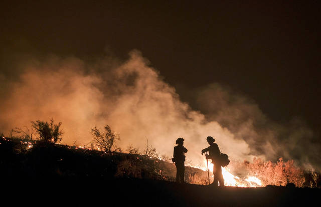 File - In this Aug. 9, 2018, file photo, firefighters keep watch the Holy Fire burning in the Cleveland National Forest in Lake Elsinore, Calif. Researchers have expanded a health-monitoring study of wildland firefighters after a previous study found season-long health declines and deteriorating reaction times. (AP Photo/Ringo H.W. Chiu, File)