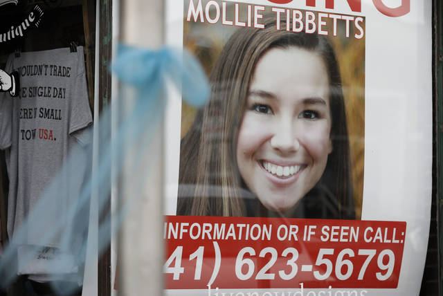 "FILE - In this Aug. 21, 2018, file photo, a poster for missing University of Iowa student Mollie Tibbetts hangs in the window of a local business in Brooklyn, Iowa. Rob Tibbetts, father of slain Iowa college student Mollie Tibbetts in a Saturday, Sept. 1, opinion piece spoke out against using his daughter's death ""to advance views she believed were profoundly racist,"" a call that comes after President Donald Trump and others seized on the suspected killer's citizenship to argue for changes in U.S. immigration laws. (AP Photo/Charlie Neibergall, File)"