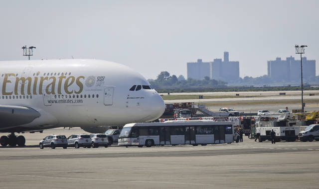 Emergency response crews gather outside a plane at New York's Kennedy Airport amid reports of ill passengers aboard a flight from Dubai, Wednesday, Sept. 5, 2018. (AP Photo/Bebeto Matthews)