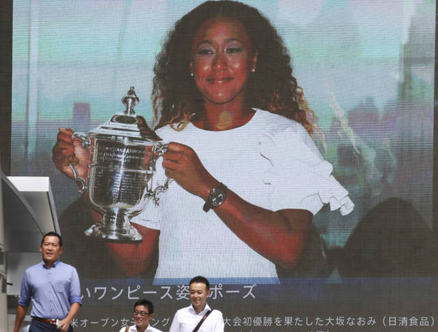 People walk by a huge screen showing US Open women's singles champion Naomi Osaka with her trophy, in Tokyo, Monday, Sept. 10, 2018. (AP Photo/Koji Sasahara)
