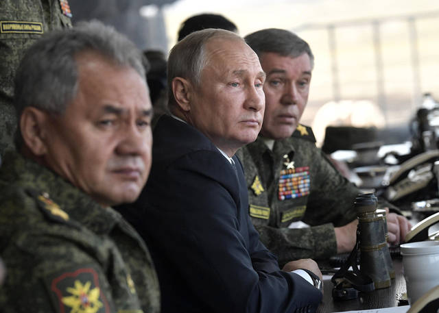 "Russian President Vladimir Putin, center, Russian Defense Minister Sergei Shoigu, left, and Head of the General Staff of the Armed Forces of Russia and First Deputy Defense Minister Valery Gerasimov watch a military exercises on training ground ""Telemba"", about 80 kilometers (50 miles ) north of the city of Chita during the military exercises Vostok 2018 in Eastern Siberia, Russia, Thursday, Sept. 13, 2018. The weeklong Vostok (East) 2018 maneuvers launched Tuesday span vast expanses of Siberia and the Far East, the Arctic and the Pacific Oceans. They involve nearly 300,000 Russian troops along with 1,000 Russian aircraft and 36,000 tanks and other combat vehicles. (Alexei Nikolsky, Sputnik, Kremlin Pool Photo via AP)"