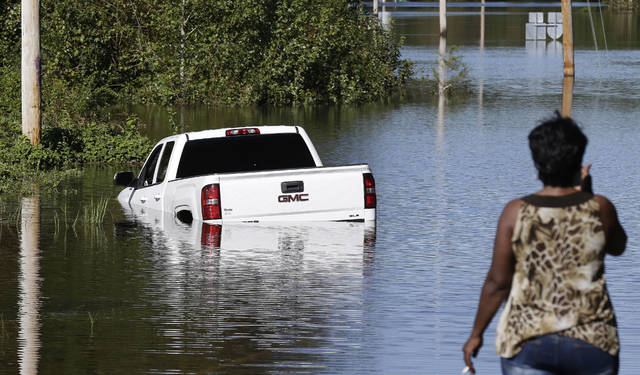 A resident surveys a road inundated by water in Lumberton, N.C., Tuesday, Sept. 18, 2018, following flooding from Hurricane Florence. (AP Photo/Gerry Broome)