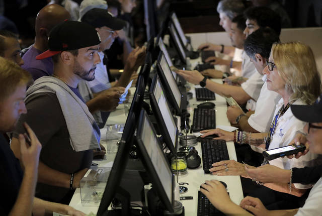 FILE - In this July 14, 2018, file photo, people, left, talk to tellers while placing bets at the Meadowlands Racetrack, in East Rutherford, N.J.   Dozens of states are rushing to capitalize on the U.S. Supreme Court lifting a federal ban on sports gambling. (AP Photo/Julio Cortez, File)