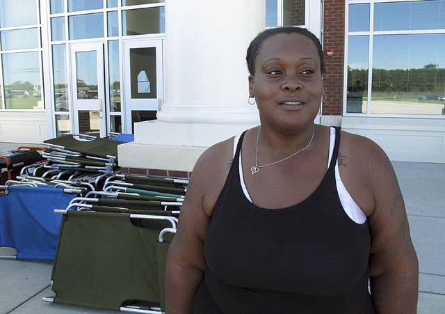 In this Tuesday, Sept. 18, 2018, photo, Lutrice Garcia stands outside a Red Cross shelter where she's staying, at a school in Bennettsville, S.C. Garcia said her nearby home was damaged by flooding caused by Hurricane Florence, and she doesn't know if she'll be able to return there to live once the water recedes. (AP Photo/Russ Bynum)