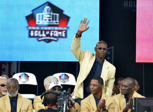 "FILE - In this Aug. 2, 2014, file photo, enshrinee Eric Dickerson is introduced during the Pro Football Hall of Fame enshrinement ceremony, in Canton, Ohio. A group of Pro Football Hall of Famers is demanding health insurance coverage and a share of NFL revenues or else those former players will boycott the induction ceremonies. In a letter sent to NFL Commissioner Roger Goodell, NFLPA Executive Director DeMaurice Smith and Hall of Fame President David Baker — and obtained by The Associated Press — 21 Hall of Fame members cited themselves as ""integral to the creation of the modern NFL, which in 2017 generated $14 billion in revenue."" Among the signees were Eric Dickerson. (AP Photo/David Richard, File)"