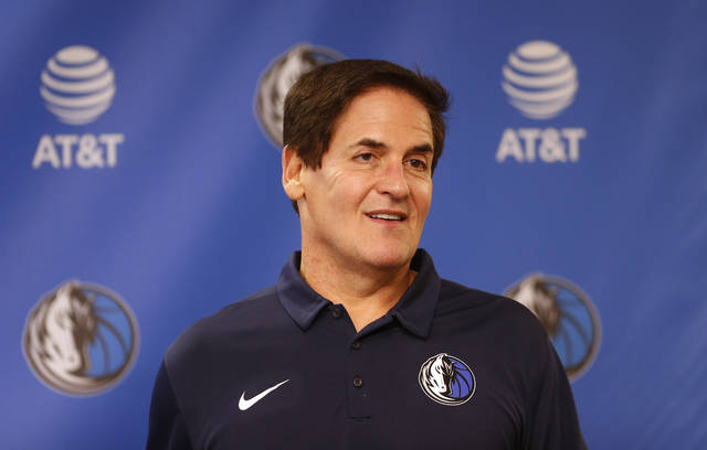 FILE - In tis Feb. 26, 2018, file photo, Dallas Mavericks owner Mark Cuban stands on stage before an NBA basketball press conference in Dallas. Cuban has agreed to contribute $10 million to women's causes and domestic violence awareness as part of the NBA's investigation into workplace conditions with his franchise. (AP Photo/Ron Jenkins, File)