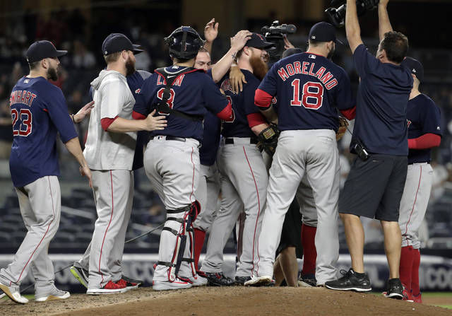 Boston Red Sox players surround relief pitcher Craig Kimbrel, center, after they defeated the New York Yankees 11-6 during a baseball game Thursday, Sept. 20, 2018, in New York. With the win, the Red Sox clinched the American League East title. (AP Photo/Julio Cortez)