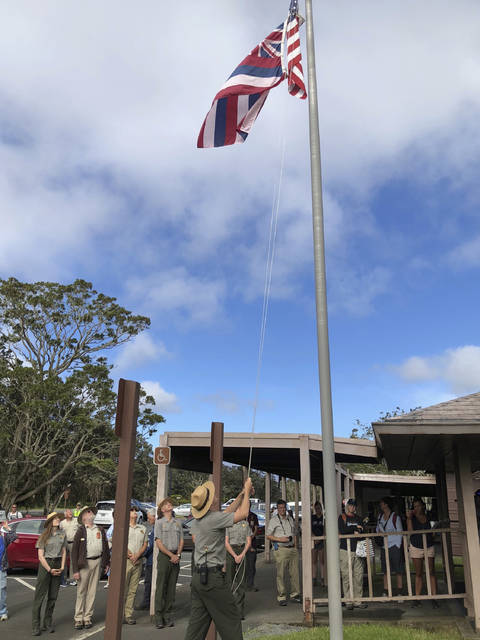 In this Saturday, Sept. 22, 2018, photo released by the National Park Service, park rangers hoist a flag on the first day Hawaii Volcanoes National Park reopened after volcanic activity forced the park to close for more than four months in Hawaii. (Janice Wei/National Park Service via AP)