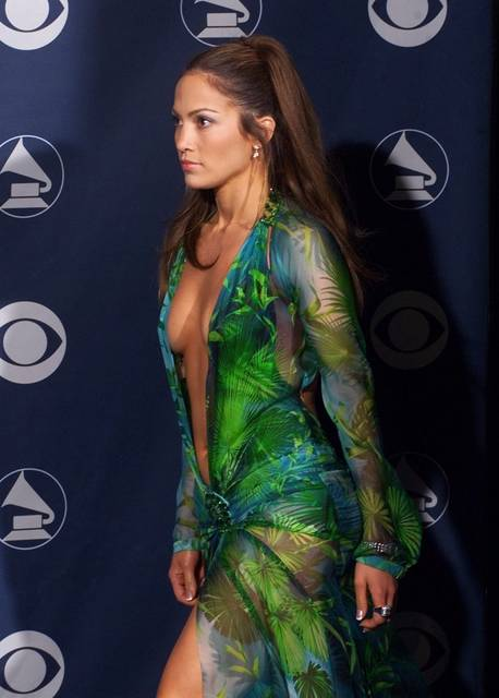 FILE - In this Feb. 23, 2000, file photo, singer Jennifer Lopez poses backstage at the 42nd Grammy Awards in Los Angeles. Michael Kors is buying the Italian fashion house Gianni Versace in a deal worth more than $2 billion (1.83 billion euros), continuing its hard charge into the world of high-end fashion. Versace is known for its Medusa-head logo and its flamboyant styles that are a fixture on Hollywood's Red Carpet - like Lopez's infamous dress worn to the Grammy Awards in 2000. (AP Photo/Reed Saxon, File)