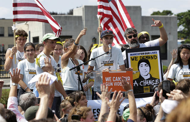 FILE - In this Sunday, Aug. 26, 2018 file photo, David Hogg, center, a survivor of the school shooting at Marjory Stoneman Douglas High School, in Parkland, Fla., addresses a rally in front of the headquarters of gun manufacturer Smith & Wesson in Springfield, Mass. The rally was held at the conclusion of a 50-mile march meant to call for gun law reforms. (AP Photo/Steven Senne)