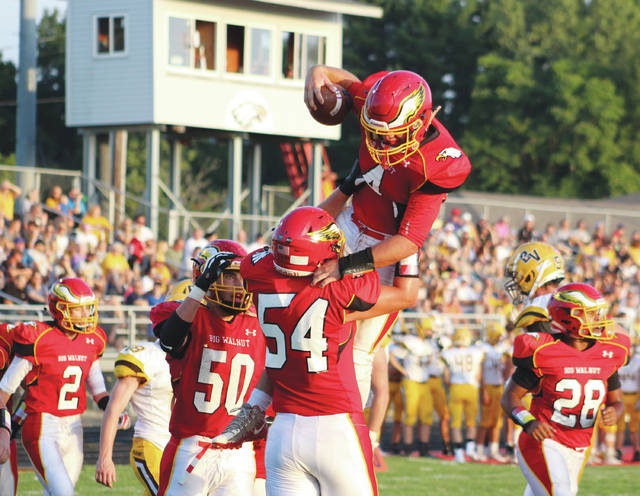 Big Walnut's Nathan Lawyer (4) is congratulated by teammates Wes Coey (54) and Josh Hageman (50) after scoring a touchdown in the first quarter of Friday's (Aug. 31) non-league showdown against visiting Buckeye Valley.