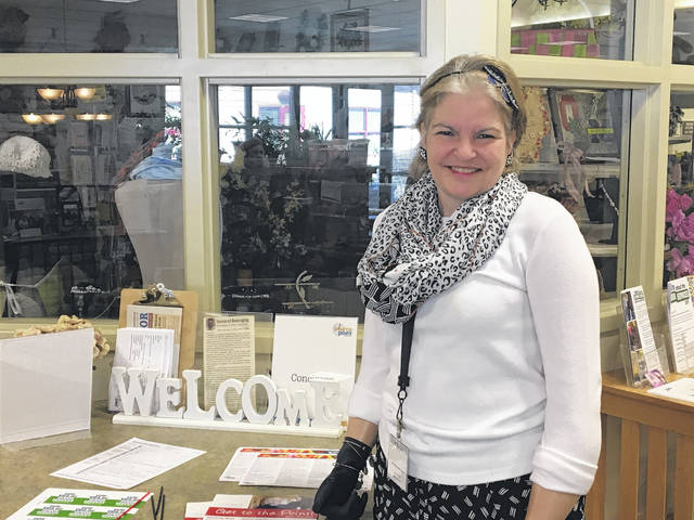 Catherine Schonauer poses for a photo Friday at the welcome table at SourcePoint's Enrichment Center. Schonauer leads tours and greets guests from 10 a.m. to noon every Friday.
