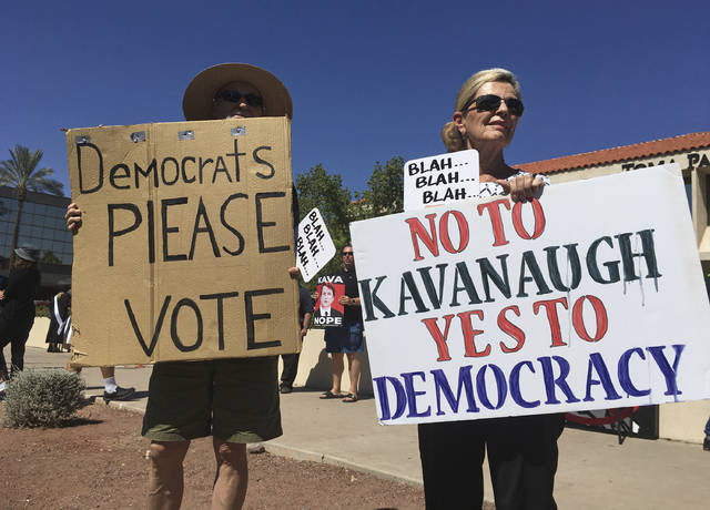 People hold up signs during a protest against Supreme Court nominee Brett Kavanaugh outside the offices of Arizona Sen. Jeff Flake in Phoenix, Friday, Sept. 28, 2018. (AP Photo/Patricio Espinoza)