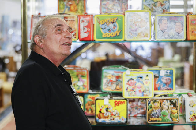 In this Friday, Sept. 21, 2018 photo, owner J. Louis Karp stands beside a case of vintage lunchboxes at Main Auction Galleries Inc., in downtown Cincinnati. Karp, a longtime auctioneer of Cincinnati-area estates has come upon a Baby Boomer delight: hundreds of vintage lunchboxes featuring the heroes of their childhood's comic books, TV shows, cartoon strips, movies and more. (AP Photo/John Minchillo)