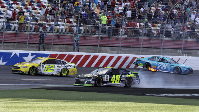 Ryan Blaney (12) drives past the wrecked cars of Jimmie Johnson (48) and Martin Truex Jr. (78) to win the NASCAR Cup series auto race at Charlotte Motor Speedway in Concord, N.C., Sunday, Sept. 30, 2018. (AP Photo/Chuck Burton)