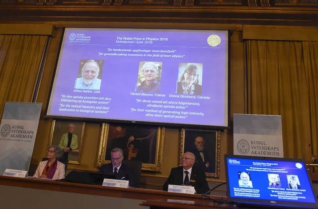 The Nobel Prize laureates for physics 2018 shown on the screen from left, Arthur Ashkin of the United States, Gerard Mourou of France and Donna Strickland of Canada during the announcement at the Royal Swedish Academy of Sciences in Stockholm, Sweden, Tuesday Oct. 2, 2018. The three scientists from the United States, France and Canada have been awarded the Nobel Prize in physics for advances in laser physics. (Hanna Franzen/TT via AP)