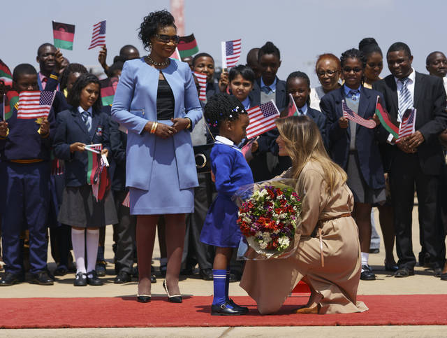 First lady Melania Trump is greeted by Malawi first lady Gertrude Maseko and a flower girl as she arrives at Lilongwe International Airport, in Lumbadzi, Malawi, Thursday, Oct. 4, 2018. Mrs. Trump is visiting Africa on her first big solo international trip, aiming to make child well-being the focus of a five-day, four-country tour. (AP Photo/Carolyn Kaster)