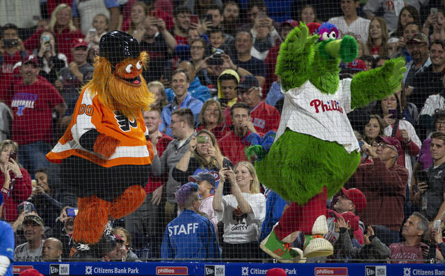 FILE - In this Sept. 29, 2018, file photo, Gritty, the Philadelphia Flyers' mascot, left, and the Philly Phanatic dance during a baseball game between the Philadelphia Phillies and the Atlanta Braves, in Philadelphia. Gritty's been loved and lampooned, swept into politics and become the orange face that launched a 1,000 memes. There's little need to play 82 games this season to find the NHL rookie of the year: it's Gritty.  (AP Photo/Laurence Kesterson, File)