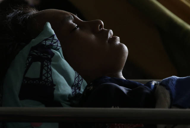 Anisa Cornelia grimaces in pain as she lies inside a medical tent after being injured in a massive earthquake and tsunami in Palu, Central Sulawesi, Indonesia Thursday, Oct. 4, 2018. All she could think of was the love of her life, the man she was supposed to marry this month. She had not seen him since a deadly tsunami smashed into the Indonesian city of Palu last week, separating the pair possibly forever as they strolled along a sandy beach at twilight. (AP Photo/Aaron Favila)