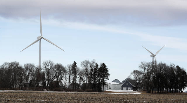 FILE - In this Feb. 2, 2018 file photo, wind turbines stand over a farmhouse  near Northwood, Iowa. A new study out of Harvard finds that ramping up wind power in America would also dial up the nation's temperatures. (AP Photo/Charlie Neibergall, File)