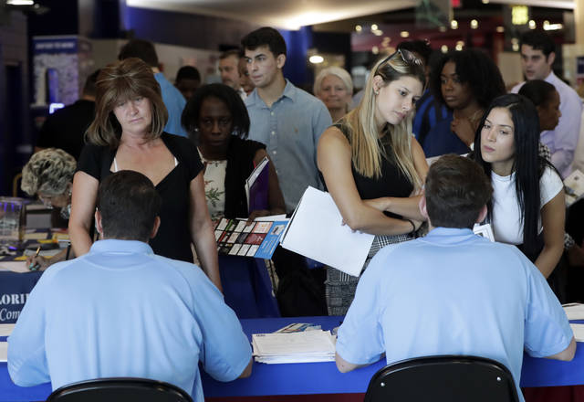 FILE- In this June 21, 2018, file photo, job applicants talks with representatives from Aldi at a job fair hosted by Job News South Florida, in Sunrise, Fla. On Friday, Oct. 5, the U.S. government issues the September  jobs report. (AP Photo/Lynne Sladky, File)