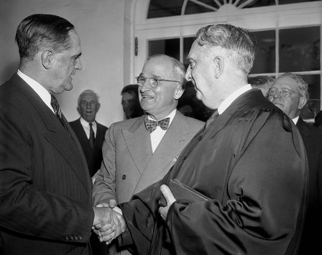 FILE - In this Oct. 12, 1949, file photo, President Harry S. Truman, center, and Chief Justice Fred Vinson, right, congratulates Sherman Minton, left, outside the White House after Minton was sworn in by Vinson as an Associate Justice of the Supreme Court, in Washington, D.C. That relationship between the White House and the Supreme Court is being examined anew following the bitter confirmation fight over Brett Kavanaugh, who angrily denounced President Donald Trump's political opponents during a Senate hearing. (AP Photo/John Rous, File)