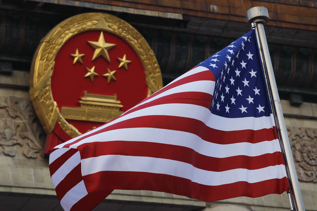 """FILE - In this Nov. 9, 2017, file photo, an American flag is flown next to the Chinese national emblem during a welcome ceremony for visiting U.S. China says accusations against an alleged spy of attempting to steal trade secrets from several American aviation and aerospace companies were """"made out of thin air."""" (AP Photo/Andy Wong, File)"""