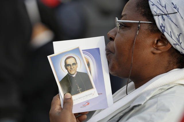A woman holds a picture of martyred Salvadoran Archbishop Oscar Romero, in St. Peter's Square at the Vatican, Sunday, Oct. 14, 2018. Pope Francis canonizes two of the most important and contested figures of the 20th-century Catholic Church, declaring Pope Paul VI and the martyred Salvadoran Archbishop Oscar Romero as models of saintliness for the faithful today. (AP Photo/Andrew Medichini)