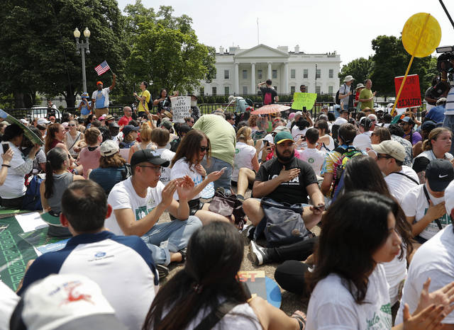 FILE - In this April 29, 2017, file photo, demonstrators sit on the ground along Pennsylvania Ave. in front of the White House in Washington. The National Park Service is exploring the question of whether it should recoup from protest organizers the cost of providing law enforcement and other support services for demonstrations held in the nation's capital. The proposed rule also could place new limits on spontaneous demonstrations and shrink a significant portion of the White House sidewalk accessible to the public. (AP Photo/Pablo Martinez Monsivais, File)