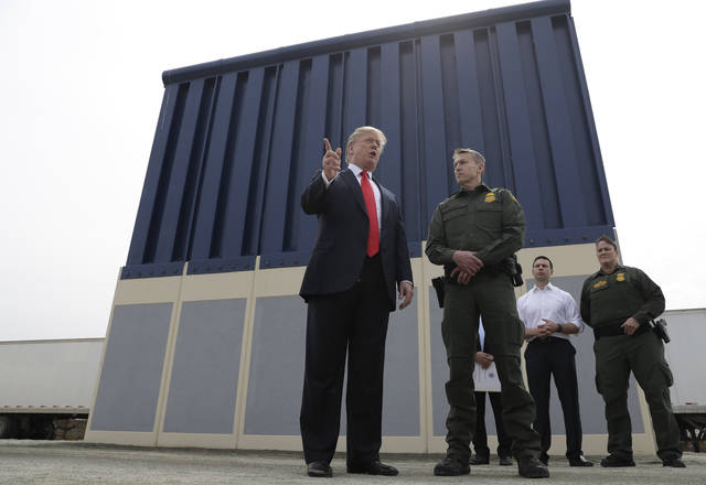 FILE - In this March 13, 2018, file photo, President Donald Trump speaks during as he reviews border wall prototypes, in San Diego, as Rodney Scott, the Border Patrol's San Diego sector chief, listens. Congress is heading toward a post-election showdown over President Donald Trump's border wall, as GOP leaders signal they're willing to engage in hardball tactics that could spark a partial government shutdown and the president revs up midterm crowds for the wall, a centerpiece of his 2016 campaign and a top White House priority. (AP Photo/Evan Vucci, File)