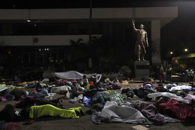 Honduran migrants hoping to reach the U.S. sleep in the southern Mexico city of Tapachula, Monday, Oct. 22, 2018, in a public plaza featuring a statue of Mexican national hero Miguel Hidalgo, a priest who launched Mexico's War of Independence in 1810. Keeping together for strength and safety in numbers, some huddled under a metal roof in the city's main plaza Sunday night. Others lay exhausted in the open air, with only thin sheets of plastic to protect them from ground soggy from an intense Sunday evening shower. (AP Photo/Moises Castillo)