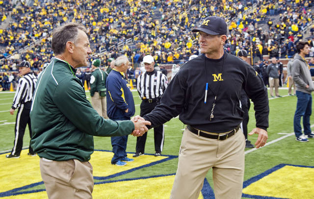 FILE - In this Oct. 17, 2015, file photo, Michigan State head coach Mark Dantonio shakes hands with Michigan head coach Jim Harbaugh on the Michigan Stadium field before an NCAA college football game in Ann Arbor, Mich. Sixth-ranked Michigan has won six straight and is in the top 10 for the first time this season. The Wolverines need to beat rival Michigan State this Saturday to keep the roll going.  (AP Photo/Tony Ding, FIle)