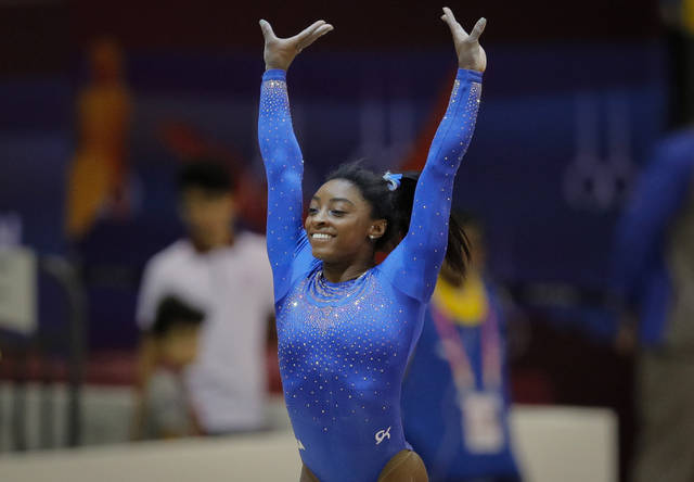 Simone Biles of the U.S. salutes fans after performing on the vault during qualifying sessions for the Gymnastics World Chamionships at the Aspire Dome in Doha, Qatar, Saturday, Oct. 27, 2018. A bout with a kidney stone did little to slow down Simone Biles, as he reigning Olympic champion easily posted the top all-around score of 60.965 during the early portions of qualifying at the 2018 world championships on Saturday, easily clearing the field and leaving little doubt that she remains atop the sport. (AP Photo/Vadim Ghirda)