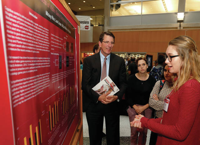 Ohio Wesleyan University President Rock Jones (left) listens with a group as student Lexi Lease discusses her Summer Science Research Program findings.