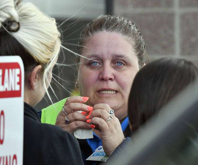 A Kroger employee wipes away tears following a shooting that left two people dead, and the subject in custody, Wednesday, Oct. 24, 2018, in Jeffersontown, Ky. (AP Photo/Timothy D. Easley)