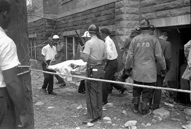 "FILE - In this Sept. 15, 1963, file photo, firefighters and ambulance attendants remove a covered body from the 16th Street Baptist Church in Birmingham, Ala., after by a deadly explosion detonated by members of the Ku Klux Klan during services. The 2018 mail-bomb scare has reopened old wounds for Lisa McNair, whose life has been shaped by the blast that occurred a year before she was born, killing her sister, Denise, 11. ""It's like, 'Ugh, again.' When are we going to get this right?"" asked McNair. ""It's been 55 years since Denise was killed. Why do we keep going there in America? Why do we keep going there as a world and human beings?"" (AP Photo)"
