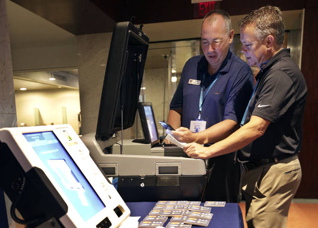 CORRECTS FROM TOM BURT TO BRYAN HOFFMAN, AND ADDS ID OF MAC BEESON - In this July 14, 2018, photo, Election Systems & Software (ES&S) VP's of Sales, Bryan Hoffman, right, and Mac Beeson look at some of the company's election equipment in the vendor display area at a National Association of Secretaries of State convention in Philadelphia. Experts say top election vendors have long skimped on security in favor of convenience and use proprietary systems, making it more difficult to detect election meddling. (AP Photo/Mel Evans)