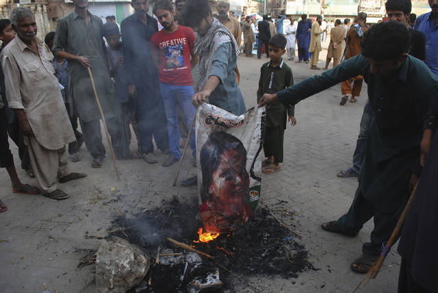 Pakistani protesters burn a poster image of Christian woman Asia Bibi, who has spent eight-years on death row accused of blasphemy and acquitted by a Supreme Court, in Hyderabad, Pakistan, Thursday, Nov. 1, 2018. Bibi plans to leave the country, her family said Thursday, as Islamists mounted rallies demanding Bibi be publicly hanged, and also called for the killing of the three judges, including Chief Justice Mian Saqib Nisar, who acquitted Bibi. (AP Photo/Pervez Masih