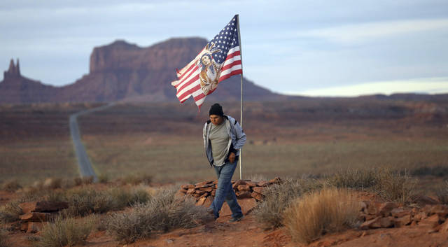 "In this Thursday, Oct. 25, 2018, photo, Brandon Nez displays his flag at near his jewelry stand in Monument Valley, Utah, where tourists stand the highway to recreate a famous running scene from the movie ""Forest Gump."". As Native American tribes around the country fight for increased access to the ballot box, Navajo voters in one Utah county could tip the balance of power in the first general election since a federal judge ordered overturned their voting districts as illegally drawn to minimize native voices. (AP Photo/Rick Bowmer)"